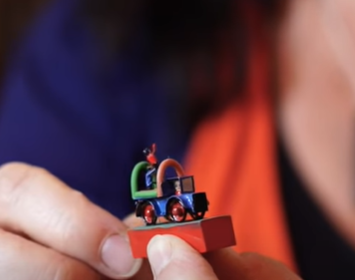 Person holding a very small toy car